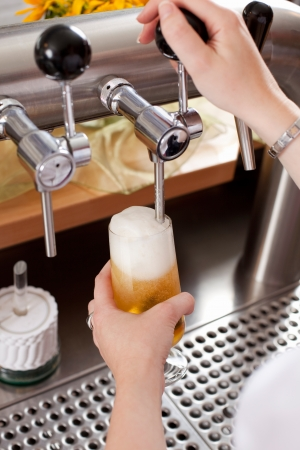 pilsner: Refreshing frothy pint of draft beer being dispensed into a glass by a bartender from a metal spigot in the keg behind the counter