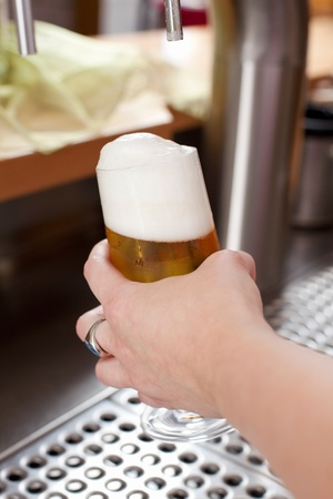 Woman holding a pint glass of draft beer with a very frothy head when dispensing it behind a bar counter photo
