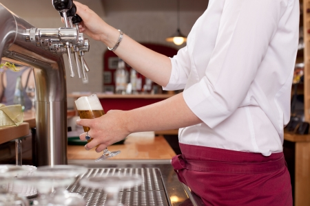 dispensing: View behind the counter of the hands of a woman dispensing draft beer in a bar from a row of metal spigots