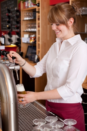 Pretty young waitress serving draft beer standing behind the bar counter dispensing it into a pint glass from a metal spigot photo