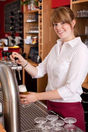 Smiling waitress pouring draft beer from a metal spigot on the keg behind the bar counter photo
