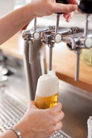 frothy: Barista versando una pinta di spumeggiante birra alla spina in un bicchiere da un rubinetto in acciaio su un barile in un bar