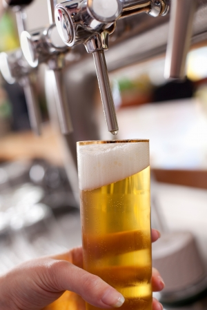 Dispensing draft beer into a pint glass at a bar or club from a metal spigot