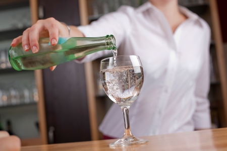 dispensing: Woman pouring a glass of mineral water into a wineglass from a glass bottle