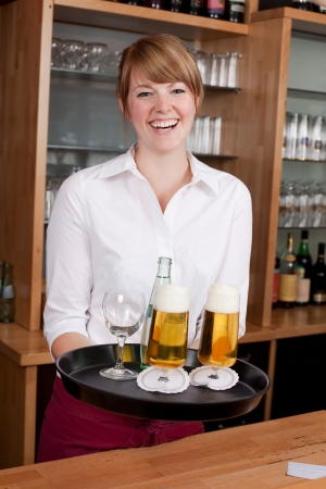 Laughing young female waitress or bartender serving drinks in a bar carrying a tray with beer and mineral water photo