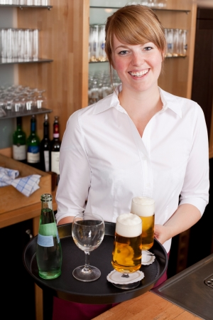 laden: Smiling friendly young waitress serving drinks in a bar carrying a tray laden with beer and a bottle of mineral water