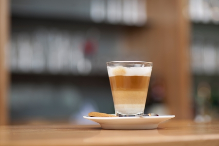 glass topped: Tempting glass of latte macchiato served layered and topped with cream on a saucer on a bar counter in a restaurant or coffee house