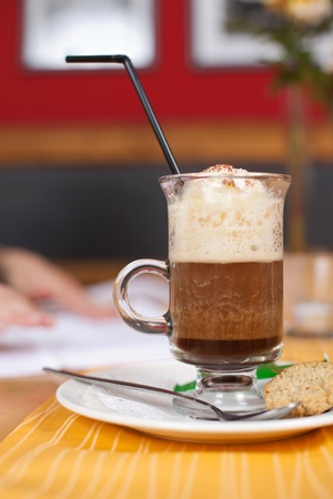 glass topped: Glass of delicious iced coffee standing on a restaurant or coffee house counter topped with rich creamy vanilla ice cream Stock Photo