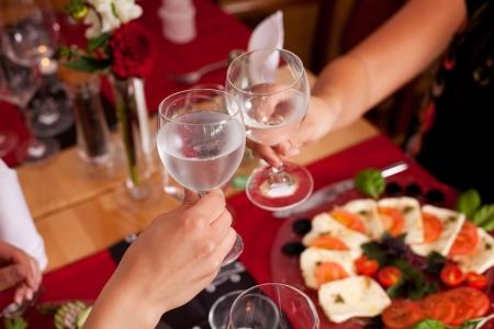vasos de agua: Brindis para el éxito y la felicidad con dos mujer levantando sus vasos de agua mineral fría en la celebración de una mesa de restaurante Foto de archivo