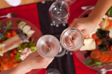 Overhead view of the hands of two women toasting in a restaurant with wineglasses filled with chilled mineral water, focus to the glasses photo