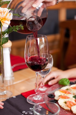 carafe: Closeup of a decanter of red wine being poured into an elegant long stemmed wineglass at a restuarant table Stock Photo