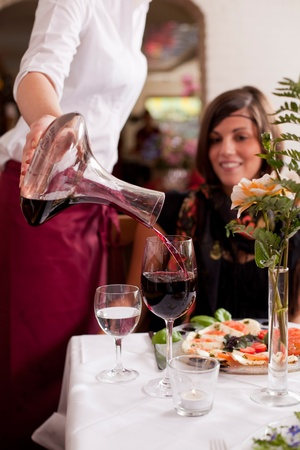 carafe: Waitress serving red wine in a restaurant watched by the customer seated at the dining table, closeup of the hands Stock Photo