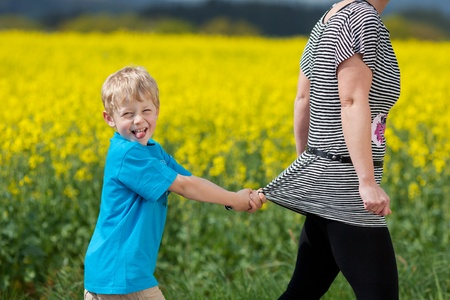 naughty boy: naughty little boy pulling his mom back while walking outside