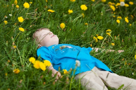 portrait of a relaxed little boy sleeping on green grass photo