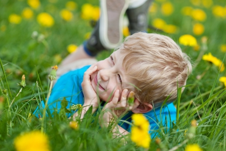 portrait of a cute boy lying on grass and looking up photo