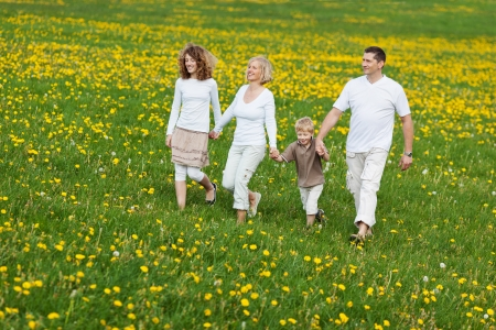 family going for a walk over green field photo
