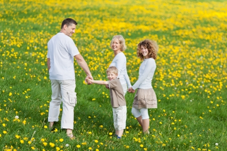family walking on grassy field looking back photo