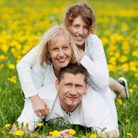 happy family lying outside on grassy field photo