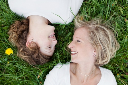 grown ups: mother and daughter looking at each other lying on green grass Stock Photo