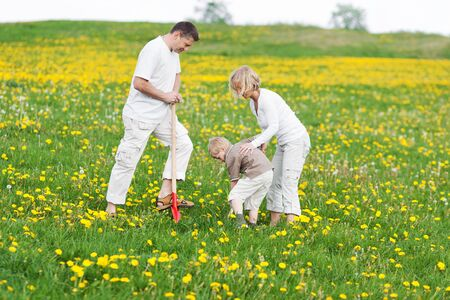 portrait of a happy family working with a spade on grassy field Stock Photo - 21301524