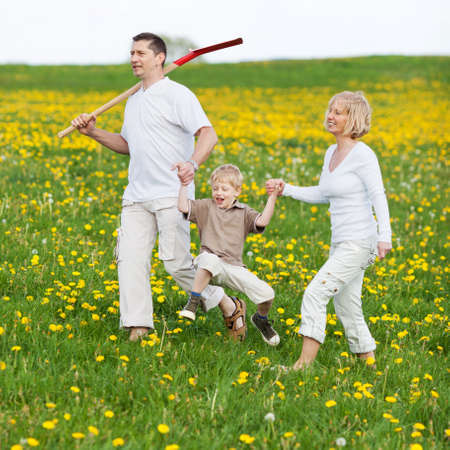 happy family walking over green field with a spade Stock Photo - 21301527