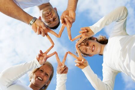 multiple family: parents and teenage daughter shaping a star with fingers Stock Photo