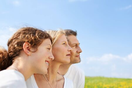 happy family standing close together against blue sky photo