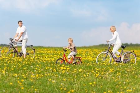 al aire libre: ciclismo familia feliz a través de campos verdes con flores