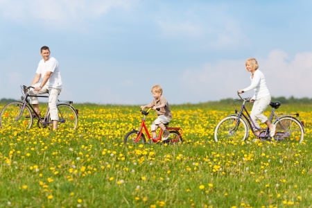 and activities: happy family cycling through green fields with flowers