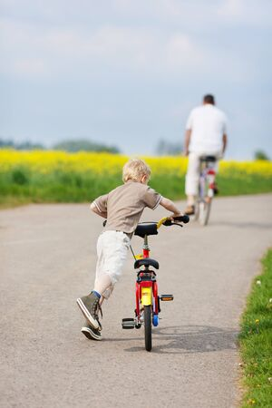 rear view of father and son riding bikes photo