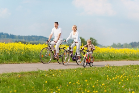 bikes: happy family riding bikes in green landscape