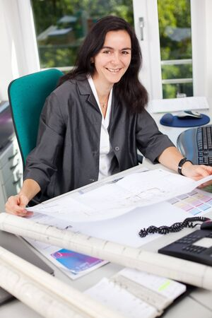 Portrait of happy female architect holding blueprint at office desk photo