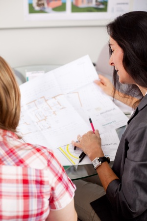 Female architect explaining blueprint to client at office desk photo
