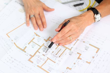 female architect with pencil pointing on plan photo