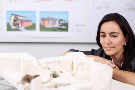 thoughful: middle agesd female architect looking thoughful on model Stock Photo