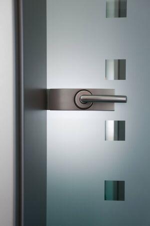 security door: view on an modern door´s handlle and glass door Stock Photo