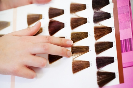 hair highlights: Closeup of clients hand choosing color from hair samples in salon