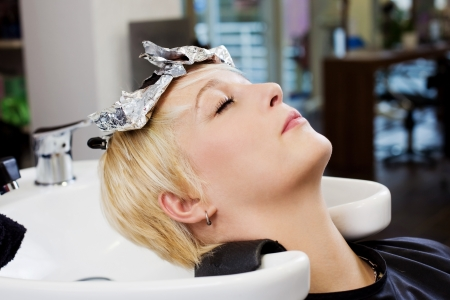 Closeup of client resting head on washbasin in salon photo