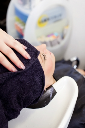 Closeup of hairdresser's hand wrapping towel on client's hair in salon photo