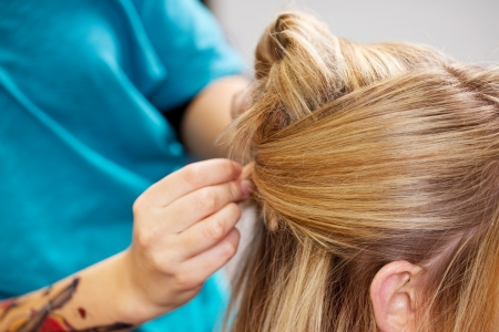 hairdo: young worker pinning up clients hair in salon Stock Photo