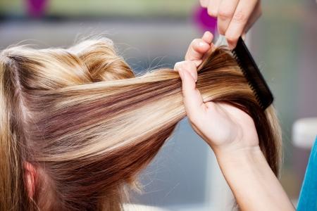 hair: Closeup of hair dresser combing clients hair in salon