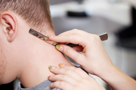 Closeup of hairdresser using razor to cut male client's hair in salon Stock Photo - 21299613