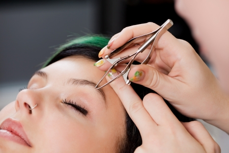 Closeup of hairdressers hands using tweezers on womans eyebrow at salon