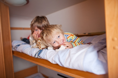 Portrait of happy young boy with brother lying on bunk bed at home photo