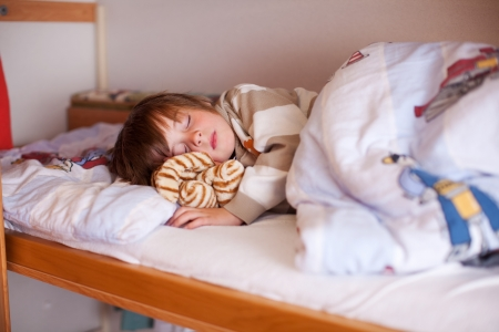 Cute little boy sleeping on bunk bed at hole photo