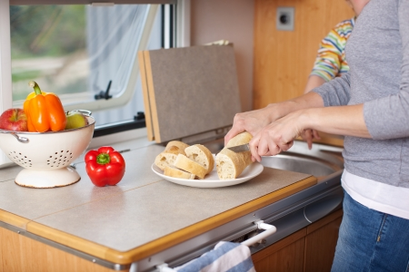 Midsection of woman cutting beadloaf at cabinet in caravan photo