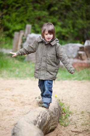 balance beam: Young boy in jacket walking on wood at park