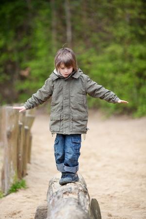 balance beam: Little boy in jacket walking on wood at park Stock Photo