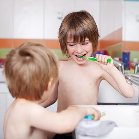 hombre sin camisa: Muchacho joven feliz cepillarse los dientes mientras mira hermano en el baño Foto de archivo