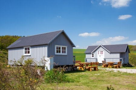Camping houses and benched on grassy field against sky
